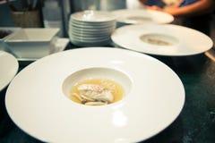 Chef-kok in hotel of restaurantkeuken die en voedsel voor diner koken verfraaien Royalty-vrije Stock Fotografie