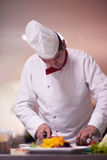 Chef-kok in hotelkeuken die en voedsel voorbereiden verfraaien Stock Foto