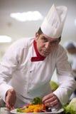 Chef-kok in hotelkeuken die en voedsel voorbereiden verfraaien Stock Foto's