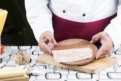 Chef-kok huidig bacon voor het koken spaghetticarbonara Royalty-vrije Stock Foto