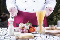 Chef-kok huidig ingrediënt van spaghetticarbonara Stock Foto's