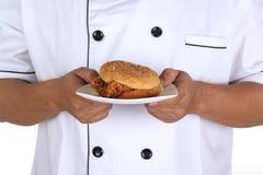 Chef-kok huidige Hamburger Stock Afbeelding