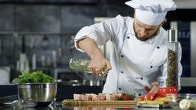 Chef-kok kokend vlees bij professionele keuken Portret van chef-kok die ruw lapje vlees koken stock video