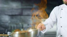 Chef-kok kokend voedsel met brandvlam in pan bij keuken Chef-kokhanden die voedsel voorbereiden stock videobeelden