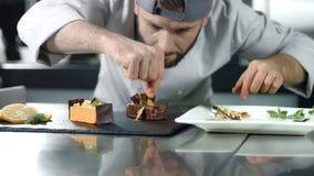 Chef-kok kokende cake bij keuken Close-upchef-kok die dessert in langzame motie verfraaien stock videobeelden