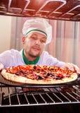 Chef-kok kokende pizza in de oven Royalty-vrije Stock Foto