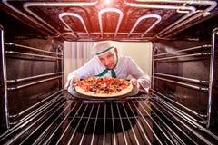 Chef-kok kokende pizza in de oven Stock Afbeeldingen