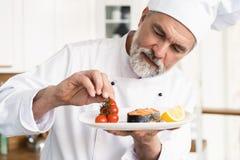 Chef-kok met ijver het eindigen schotel op plaat, vissen met groenten stock afbeelding