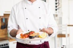Chef-kok met ijver het eindigen schotel op plaat, vissen met groenten royalty-vrije stock afbeelding