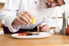Chef-kok met ijver het eindigen schotel op plaat, vissen met groenten stock foto's