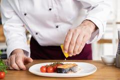 Chef-kok met ijver het eindigen schotel op plaat, vissen met groenten royalty-vrije stock foto's
