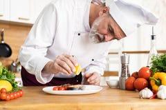 Chef-kok met ijver het eindigen schotel op plaat, vissen met groenten royalty-vrije stock fotografie