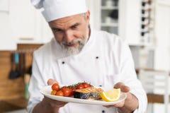 Chef-kok met ijver het eindigen schotel op plaat, vissen met groenten stock fotografie
