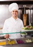 Chef-kok met kebab bij fastfood Stock Afbeeldingen