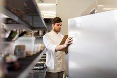Chef-kok met klembord die inventaris doen bij keuken stock foto's