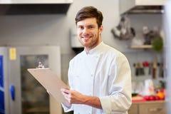 Chef-kok met klembord die inventaris doen bij restaurant stock fotografie