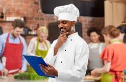 Chef-kok met menu op klembord bij het koken van klasse royalty-vrije stock afbeeldingen