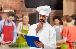 Chef-kok met menu op klembord bij het koken van klasse royalty-vrije stock fotografie