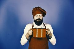 Chef-kok met rode braadpan of steelpan De mens met baard houdt keukengerei op blauwe achtergrond royalty-vrije stock fotografie