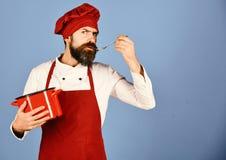 Chef-kok met rood braadpan en bestek Kok met ernstig gezicht royalty-vrije stock afbeeldingen