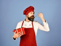 Chef-kok met rood braadpan en bestek Professioneel het kokenconcept stock fotografie