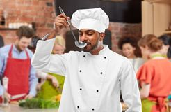Chef-kok proevend voedsel van gietlepel bij het koken van klasse stock fotografie