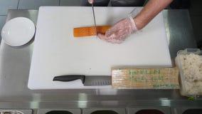 Chef-kok in restaurant die en het Snijden het gezonde voedsel van sushibroodjes voorbereidingen treffen Hoogste mening Royalty-vrije Stock Foto