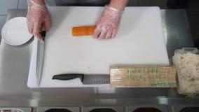 Chef-kok in restaurant die en het Snijden het gezonde voedsel van sushibroodjes voorbereidingen treffen Hoogste mening Stock Afbeeldingen
