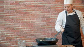Chef-kok in restaurant die gebraden bol met zeevruchten in pan koken, die citroensap drukken stock footage