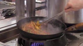 Chef-kok in restaurantkeuken bij fornuis met wokpan, de garnalenzeevruchten van mengelingsgroenten stock footage