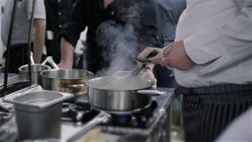 Chef-kok ` s Masterclass Chef-kok Stirs Boiling Souce in Pan In een Commerciële Keuken stock video