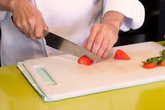 Chef-kok scherpe aardbei royalty-vrije stock foto