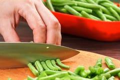 Chef-kok scherpe bonen voor het koken Voorraad omhoog op de wintervoedsel stock afbeelding