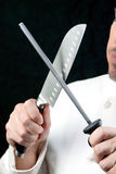 Chef-kok Sharpens Knife, Kant Stock Afbeeldingen