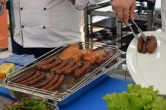 Chef-kok voor het koken van worsten en geroosterd vlees Stock Afbeelding