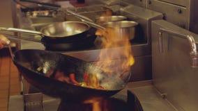 Chef-kok werpen die beweegt gebraden gerecht vlammen stock videobeelden