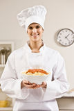 Chef-kok in wit dat trots kom voedsel houden Stock Foto