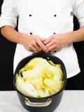 Chef-kok in witte jasjeholding rond een braadpan royalty-vrije stock afbeelding