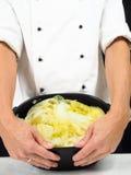 Chef-kok in witte jasjeholding rond een braadpan van gekookt cabbag royalty-vrije stock foto