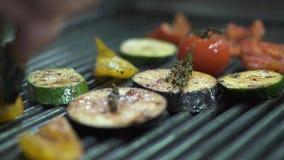 Chef-kokhand die groententomaat, aubergine, courgette, gele groene paprika op de grill controleren die metaaltang dicht uitputten stock videobeelden