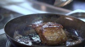 Chef-kokhand die sappige ribben op de gekregen pan met het vet gieten om de schotel sappiger en zacht te maken Kok het voorbereid stock videobeelden