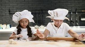 Chef-kokjong geitje De keuken van het twee jonge geitjesspel Weinig jongen en peuterjongen in chef-kokhoeden en schorten rollen d stock videobeelden