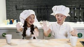 Chef-kokjong geitje Twee jonge geitjes in chef-kokhoeden die met deeg spelen Het hebben van pret in huiskeuken Het voorbereiden v stock video