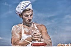 Chef-kokkok die deeg voor baksel met bloem voorbereiden Baker concept De mens op bezig gezicht draagt kokende hoed en schort, hem royalty-vrije stock afbeeldingen