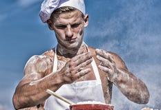 Chef-kokkok die deeg voor baksel met bloem voorbereiden De mens op bezig gezicht draagt kokende hoed en schort, hemel op achtergr royalty-vrije stock foto
