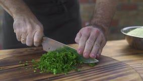 Chef-kokkok die groene peterselie op houten raad snijden Chef-kokkok die verse peterselie op scherpe raad hakken Ingrediënt voor stock videobeelden