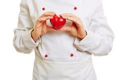 Chef-kokkok die rood hart houden Stock Foto's