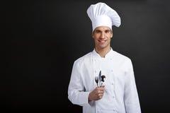 Chef-kokkok die tegen donkere achtergrond met hoeden holdinf lepel glimlacht Stock Foto