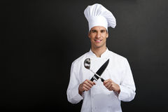 Chef-kokkok die tegen donkere achtergrond met hoeden holdinf lepel glimlacht Stock Afbeelding
