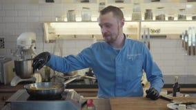 Chef-kokkooktoestel in zwarte handschoenen friyng of het stoven plakken van courgette en graan op een hete pan met olie Op de ach stock footage